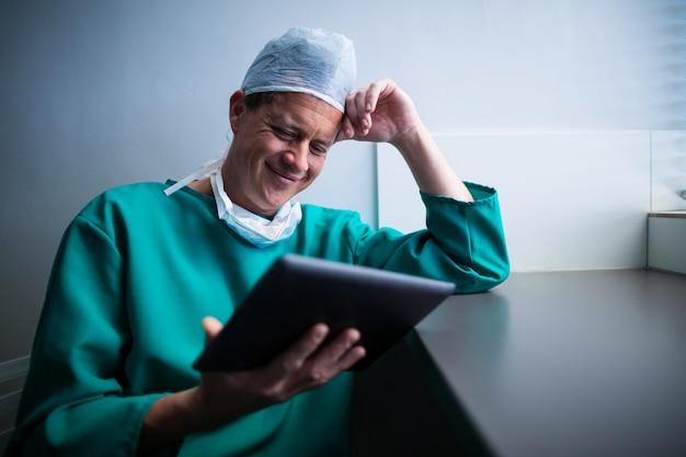 Chirurgo maschio che per mezzo della compressa digitale