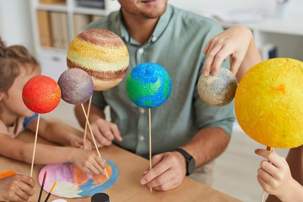 Insegnante maschio che tiene i modelli del pianeta mentre lavora con un gruppo di bambini nella lezione di arte e artigianato