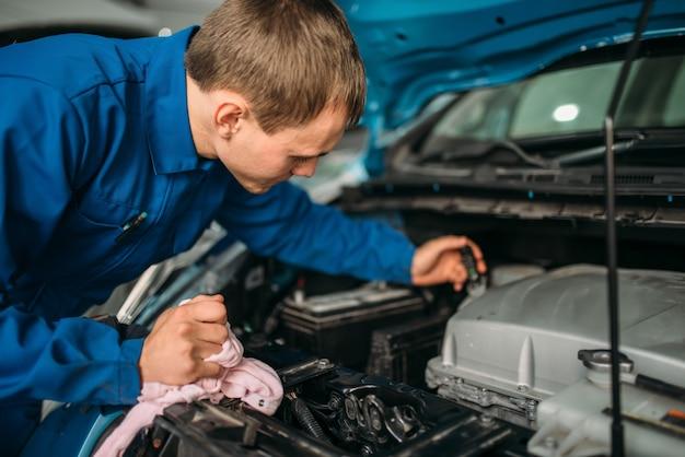 Il tecnico maschio controlla il livello del liquido dei freni in auto