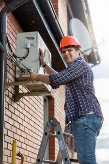 Tecnico maschio che ripara il sistema di condizionamento dell'aria esterno