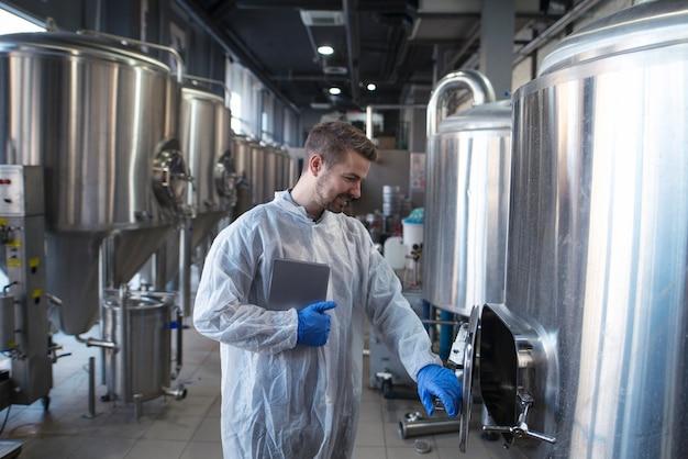 Tecnologo maschio in abbigliamento sterile e tablet che controlla la linea di produzione in fabbrica.