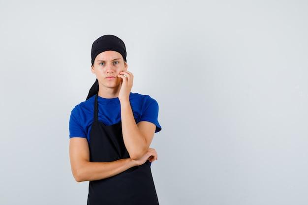 Cuoco adolescente maschio in maglietta, grembiule che tiene la mano sulla guancia e sembra dispiaciuto, vista frontale.