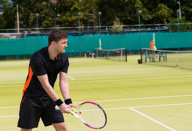 Giocatore di tennis maschio si prepara a servire indossando un abbigliamento sportivo durante la partita su un campo all'aperto in estate o in primavera