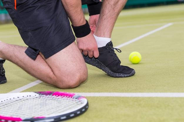 Giocatore di tennis maschio che lega i lacci delle scarpe ha lasciato la racchetta e la palla su un campo all'aperto in estate o in primavera