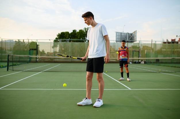 Giocatori di tennis maschi con le racchette colpisce le palline, allenandosi su un campo all'aperto. stile di vita sano attivo, le persone giocano a giochi sportivi, allenamento fitness con racchette
