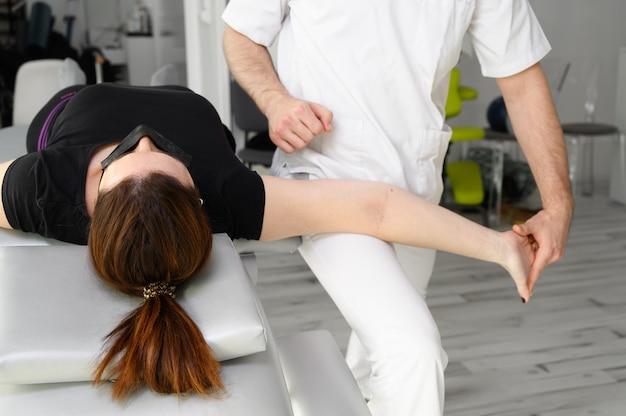 Terapista maschio che dà massaggio per alleviare il dolore alla spalla a una paziente in fisioterapia.