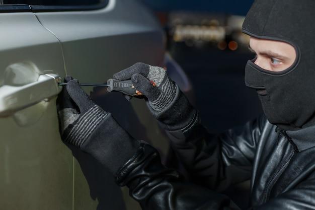 Le mani del ladro maschio aprono la portiera della macchina con un cacciavite