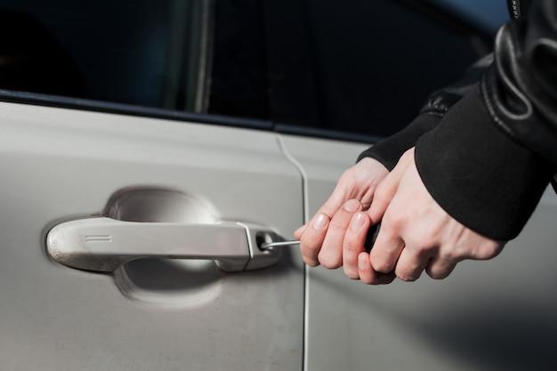 Mani di ladro maschio che cercano di aprire la portiera della macchina con un cacciavite. carjacker sblocca il veicolo. pericolo di furto d'auto