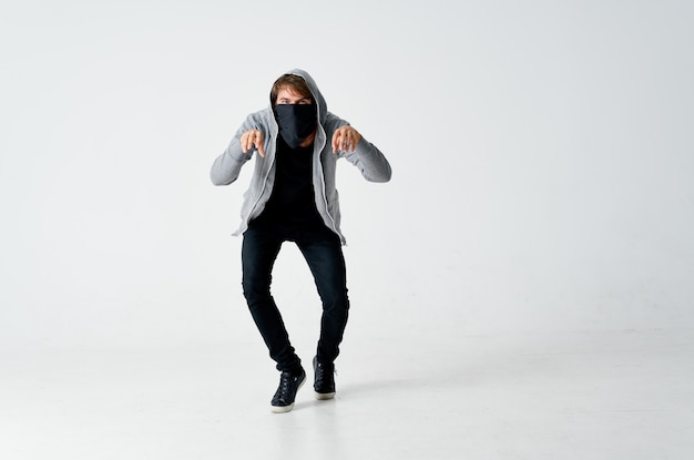Ladro maschio in fondo isolato in punta di piedi maschera nascosta cappuccio