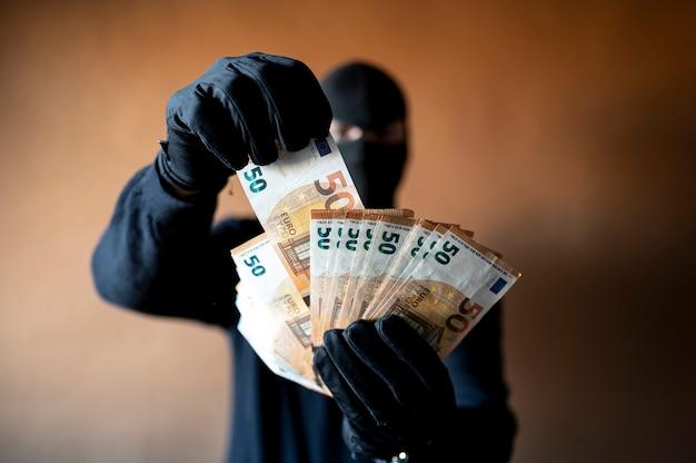Ladro maschio con passamontagna in testa che tiene una manciata di banconote in euro a ventaglio