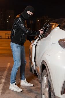 Ladro maschio con passamontagna in testa che apre la portiera della macchina. pericolo di furto d'auto, concetto di marketing di assicurazione auto.