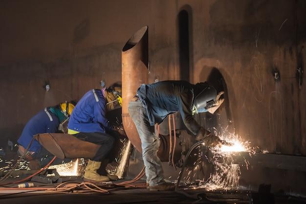 Tre lavoratori di sesso maschile che indossano indumenti protettivi e riparano il serbatoio di stoccaggio della piastra del guscio del serbatoio di saldatura all'interno di spazi ristretti