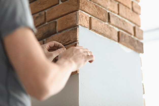 Piastrellista maschio sta posando piastrelle a forma di mattone su una colonna di cemento