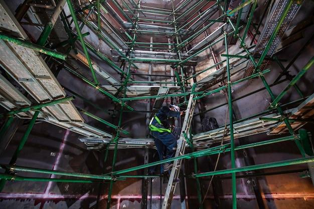 La vista dall'alto maschile sale la vasca di ispezione dell'impalcatura delle scale all'interno di uno spazio ristretto