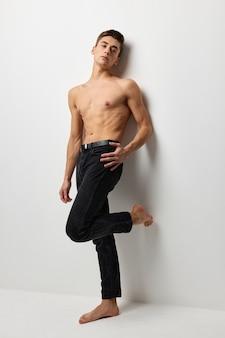 Pantaloni neri in topless maschile in posa modello di moda di lusso.
