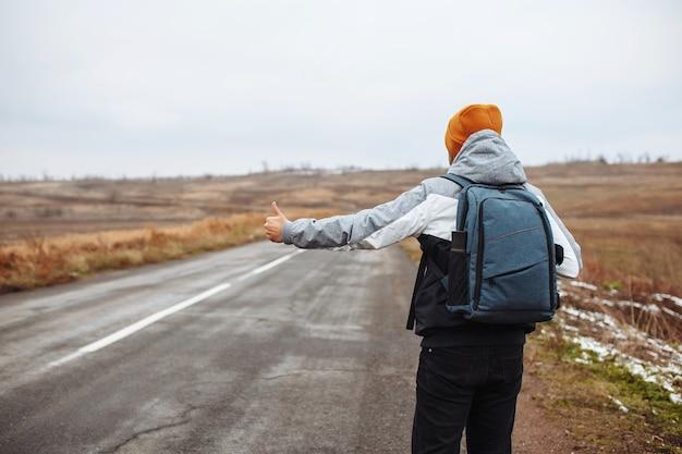 Il turista maschio prende un'auto sul lato di una strada invernale vuota nella zona suburbana con uno zaino. un uomo che indossa un cappello arancione su un'autostrada.