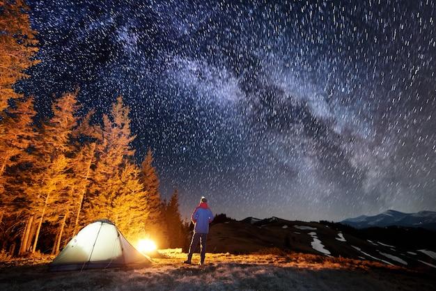 Il turista maschio si riposa nel suo accampamento vicino alla foresta di notte. uomo in piedi vicino al fuoco e tenda sotto il bellissimo cielo notturno pieno di stelle e via lattea