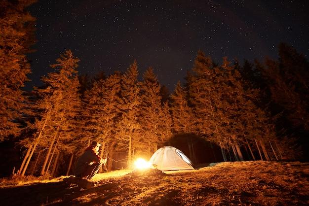 Il turista maschio si riposa nel suo accampamento vicino alla foresta di notte, seduto vicino al fuoco e alla tenda