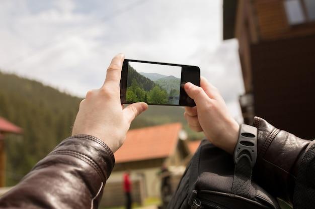 Turista maschio che cattura foto nelle montagne dei carpazi sul suo smartphone
