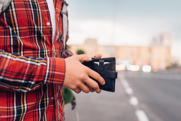 Turista maschio con portafoglio alla fermata dell'autobus. viaggio estivo, escursione avventura su visite turistiche, passeggiate in città, concetto di escursionismo