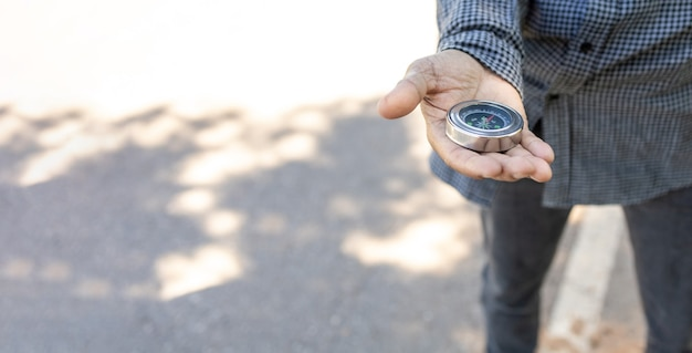 Viaggiatore maschio che tiene una bussola magnetica su strada asfaltata, orientamento e trovare la strada.