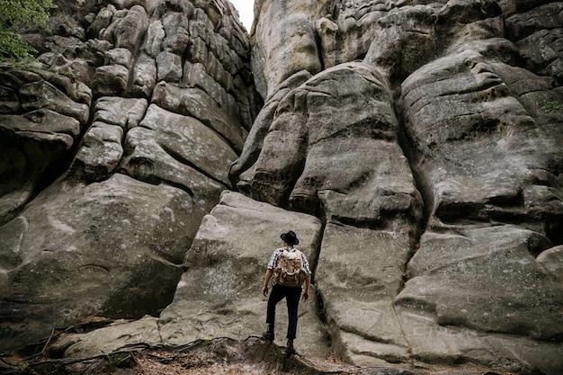 Un viaggiatore maschio sta con uno zaino davanti a una grande roccia in montagna