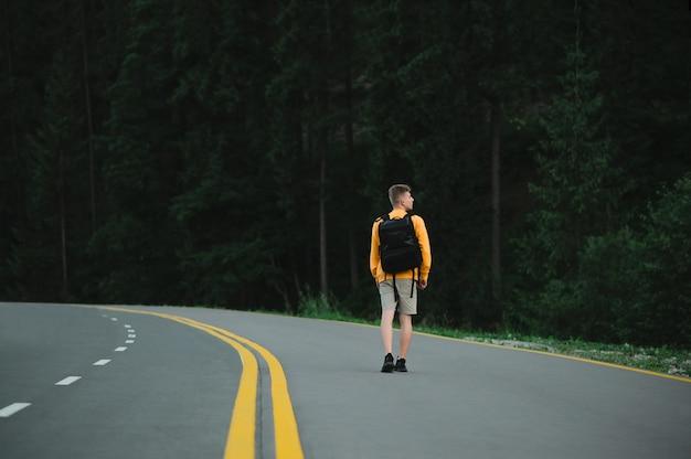 Viaggiatore maschio che cammina lungo la strada asfaltata la sera guardando la foresta di conifere di montagna