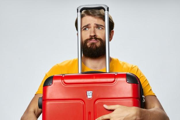 Viaggiatore maschio con una valigia in mano in posa in studio, vacanza
