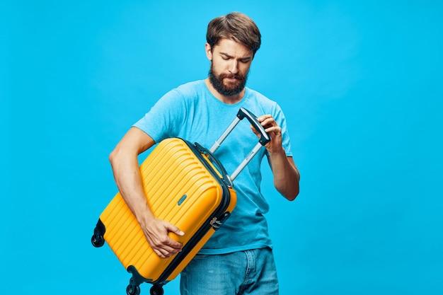 Viaggiatore maschio con una valigia in mano in posa in studio