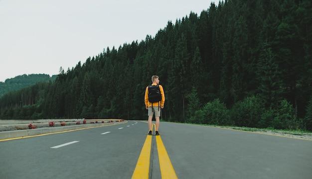 Viaggiatore maschio in felpa gialla in piedi in mezzo alla strada al paesaggio della foresta di montagna