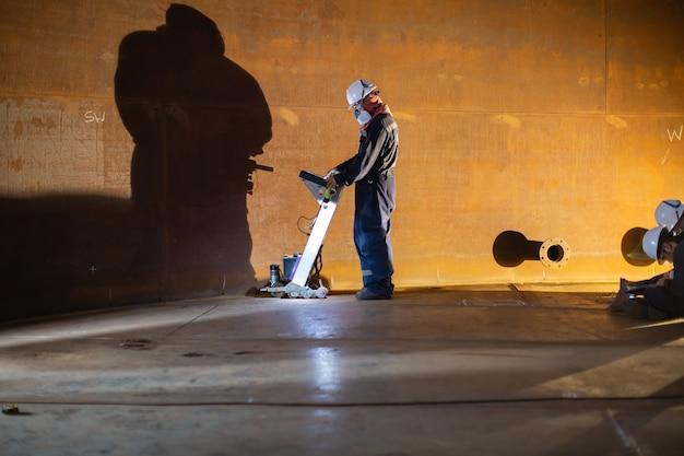 Il serbatoio di scansione del pavimento di ispezione di due lavoratori maschi della parete di ruggine perde lo spessore della piastra inferiore in confinato