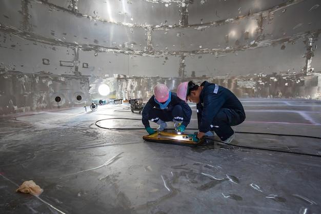 Maschio due lavoratori ispezione vuoto prova piastra inferiore serbatoio sciroppo di glucosio acciaio saldatura perdite specifiche interne confinate