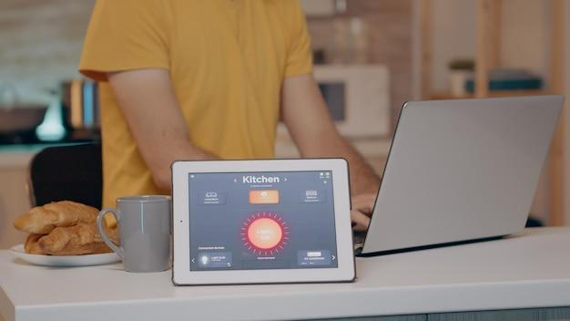 Digitazione maschile su laptop che lavora da casa con sistema di illuminazione automatizzata utilizzando un'app a comando vocale su tablet che accende la luce. il gadget intelligente risponde ai comandi, l'uomo controlla l'elettricità
