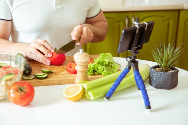Vlogger maschio che registra una ricetta vegetale sana blog culinario per vegetariani