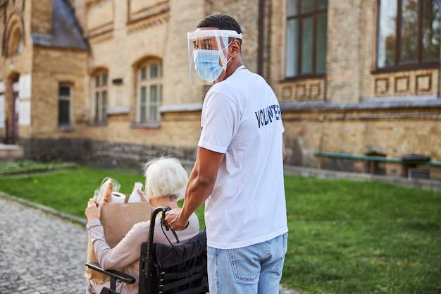 Volontario maschio che gira la testa all'indietro mentre spinge una sedia a rotelle del suo residente della casa di cura per anziani