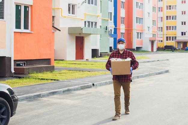 Un volontario maschio che indossa una maschera protettiva cammina per strada con una scatola di generi alimentari, carità.