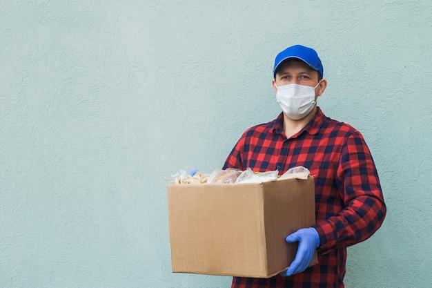 Volontario maschio che indossa una maschera protettiva con una scatola di generi alimentari, carità.