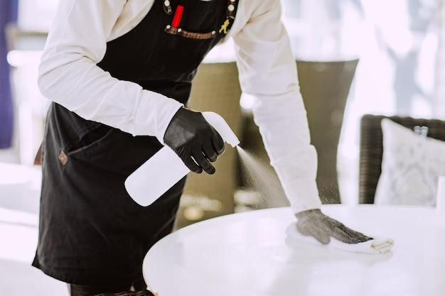 Cameriere maschio in grembiule nero, maschera medica e guanti che puliscono il tavolo bianco al ristorante con la bottiglia di disinfezione.