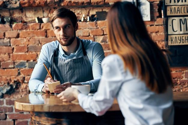 Cameriere maschio in grembiuli grigi prende un ordine e una tazza di caffè cliente femminile a un tavolo in un bar
