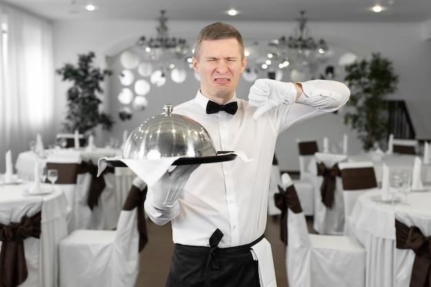 Il cameriere maschio in un ristorante con un piatto in mano mostra che questo piatto è insapore.