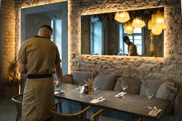Il cameriere maschio serve stoviglie sul tavolo del ristorante