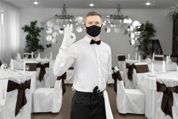 Un cameriere maschio con una camicia bianca e una maschera medica protettiva nella sala del ristorante mostra il segno