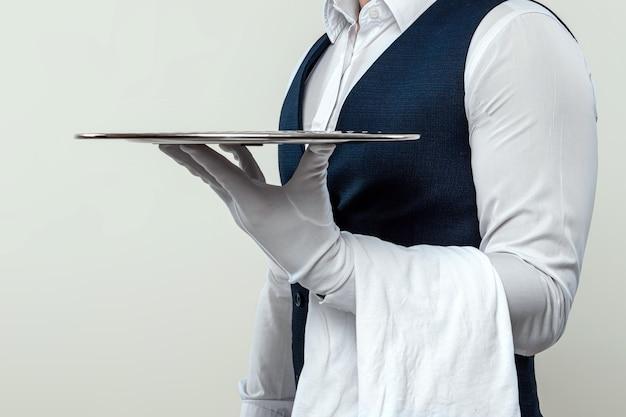 Un cameriere maschio con una camicia bianca e guanti bianchi è in piedi di lato con un vassoio d'argento. il concetto di personale di servizio che serve i clienti in un ristorante.