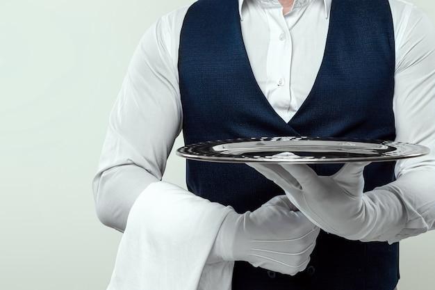 Un cameriere maschio con una camicia bianca e guanti bianchi sta con un vassoio d'argento. il concetto di personale di servizio che serve i clienti in un ristorante.