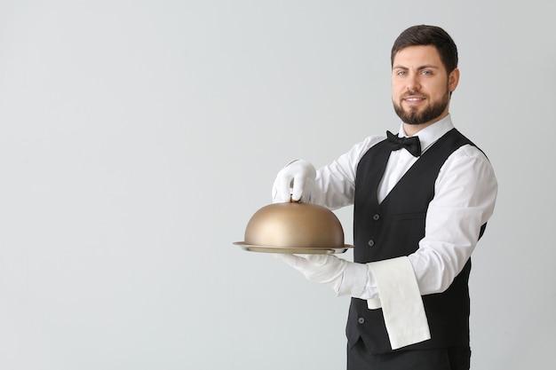 Cameriere maschio con vassoio e cloche su sfondo grigio