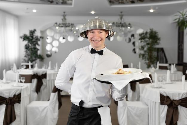 Cameriere maschio con un coperchio del vassoio sulla sua testa in un ristorante.