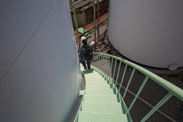 Maschio che cammina verso il basso per l'ispezione visiva della scala di ispezione del serbatoio di stoccaggio dell'imbracatura di sicurezza lavora in alto.