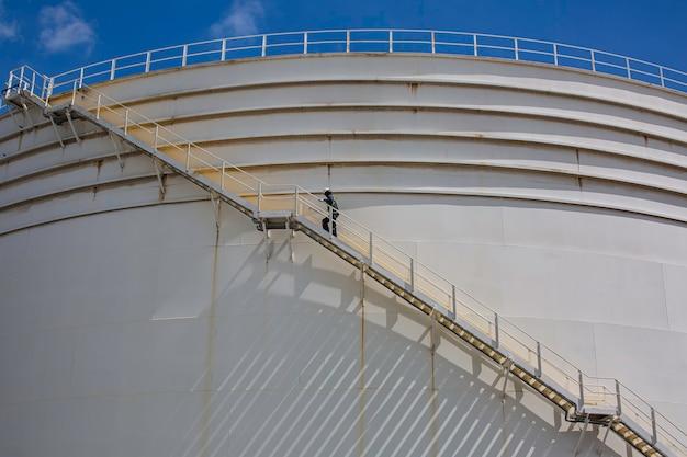 Maschio che cammina sul serbatoio di stoccaggio del record visivo di ispezione delle scale.
