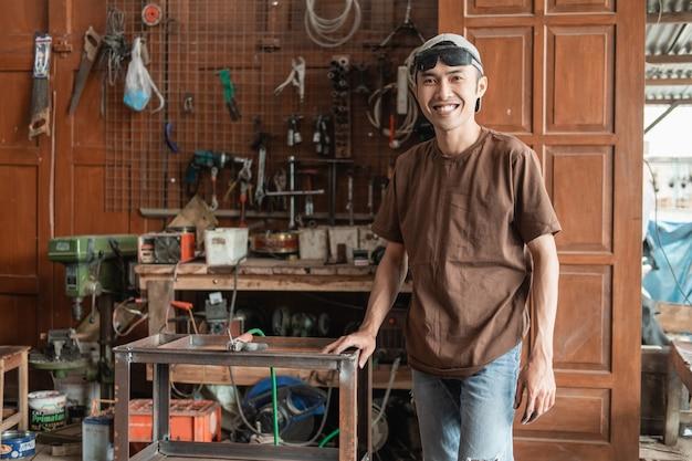 Saldatore maschio sorride alla telecamera che tiene una cremagliera metallica sullo sfondo del laboratorio di saldatura