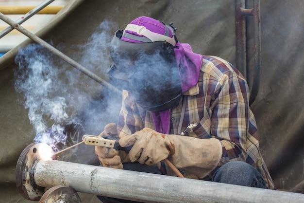 Saldatore maschio lavoratore che indossa indumenti protettivi che riparano il fumo di saldatura della conduttura di riparazione